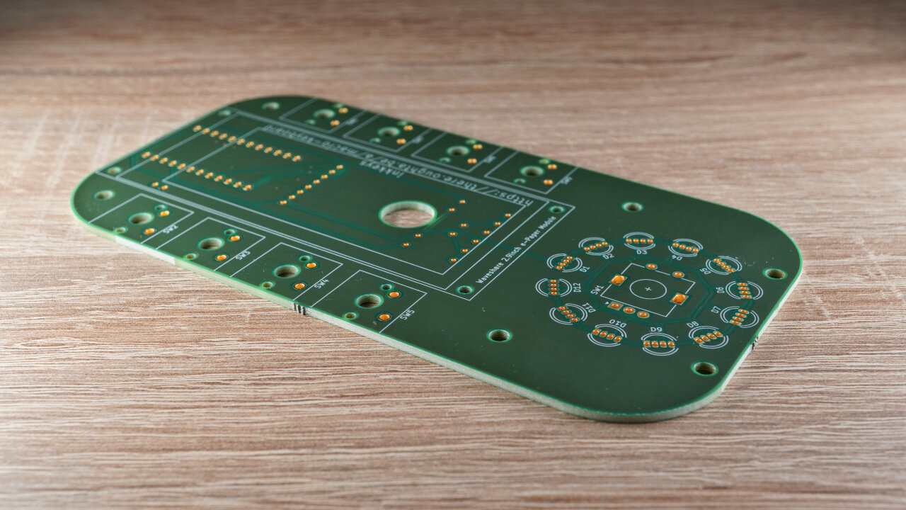 Photo of the PCB. Is rectangular with rounded corners and a hole in its center.